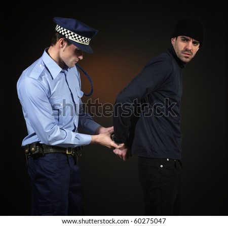Police officer arretign a thief. Dark background. Square format