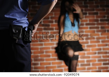 Police officer delay prostitute in front of  brick wall