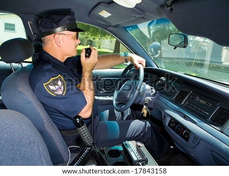 Police officer in his squad car, talking on his radio. - stock photo