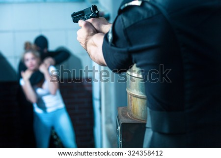 Police officer is aiming to the criminal - stock photo
