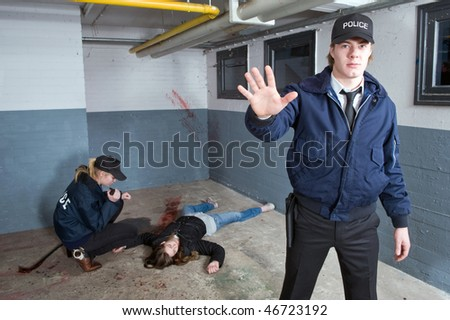 Police officer keeping bystanders at a distance from a crime scene with a murdered woman in the background