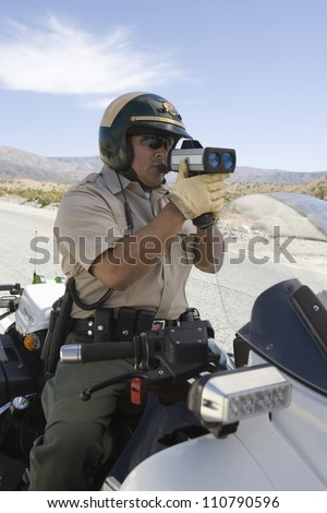 Police officer on motorbike monitoring speed though radar gun - stock photo