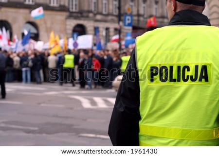 Police officer protecting an anti-government demonstration in Warsaw Poland on 7 October 2006 (Blue March by Platforma Obywatelska). Purposely taken with a shallow DOF not to detail faces. - stock photo