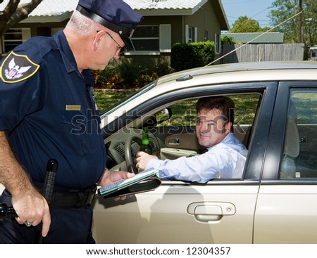 Police officer pulling over a drunk driver.  The driver is holding a beer and looking embarassed. - stock photo