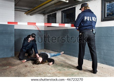 Police officer setting the perimeter of a murder scene with a colleague checking the pulse of the victim and calling for backup on her radio