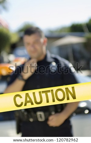 Police officer standing behind yellow caution tape - stock photo