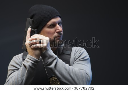 Police officer with a badge and gun, looking off camera and ready for a fight.