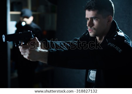 Police officer with handgun aiming at criminal - stock photo