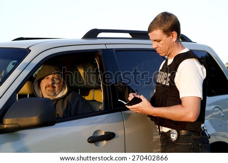 Police officer writing man ticket - stock photo
