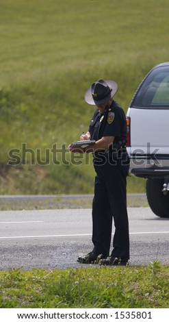 Police Officer Writing Ticket or Accident Report - stock photo