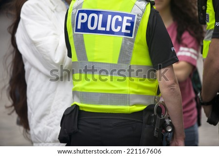 Police officers on duty. Daytime in public place outdoors. Back view - stock photo