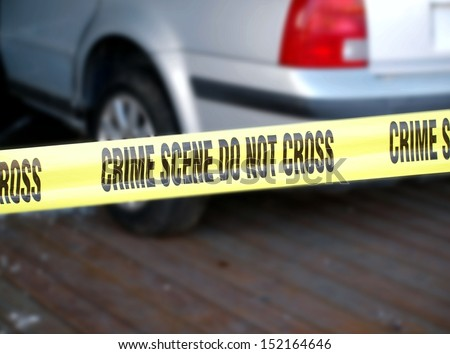 Police put up yellow tape blocking off a crime scene involving a car  - stock photo