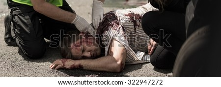 Policeman checking vital signs of victim car accident - stock photo