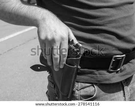 policeman put his hand on his holster with a gun - stock photo