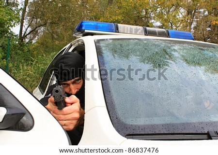 Policeman shoots from the police vehicle, detail - stock photo