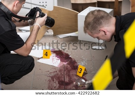 Policeman working with a magnifier, young man taking pictures of a crime scene - stock photo