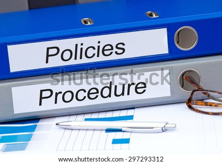 Policies and Procedure - two binders on desk in the office - stock photo