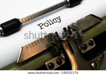 Policy on typewriter - stock photo