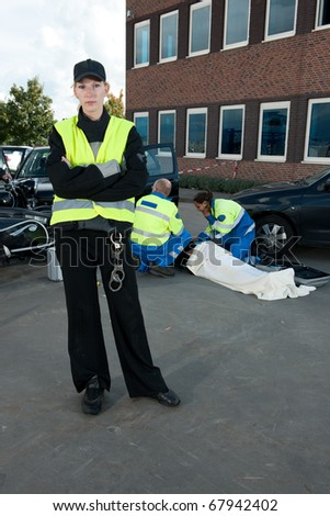 Polise woman posing for the camera at the site of a car crash, with two paramedics tending to an injured driver in the background