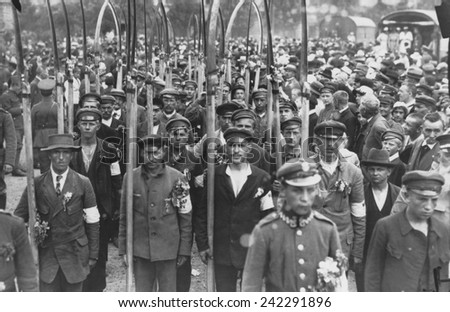 Polish army volunteers with scythes in a crowd of people in July 1920. The Russo-Polish War of 1919-20 followed the creation of the Polish Republic by the Versailles Peace Conference.