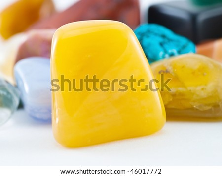 Polished yellow agate gemstone in front of gemstone collection - stock photo