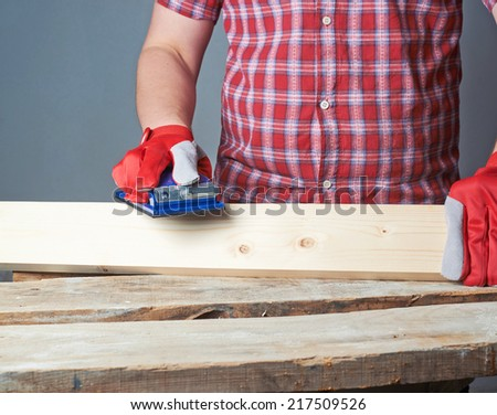 Polishing wooden pine board with the sandpaper - stock photo