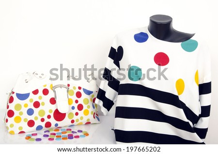 Polka dots and stripes blouse on mannequin with matching accessories. Cute blouse on tailor's dummy with purse and necklace. - stock photo