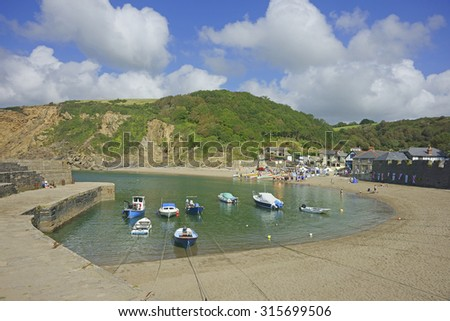 Polkerris beach and harbour, a small sandy beach sheltered by a curving harbour wall, on a beautiful summer day with blue sea and sky, South Cornwall near St Austell, United Kingdom - stock photo