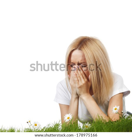 Pollen allergy, woman sneezing in a field of flowers - stock photo