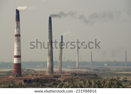 Polluting air pipes of brick factories in Dhaka, Bangladesh. - stock photo