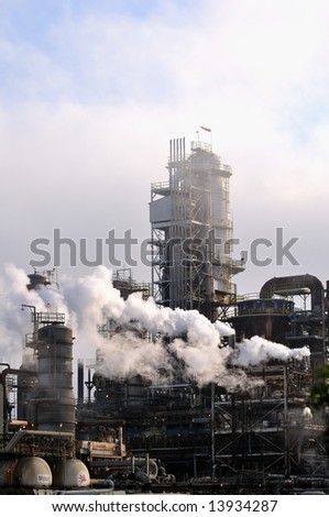 Pollution billows from the smokestacks of a large oil refinery. - stock photo