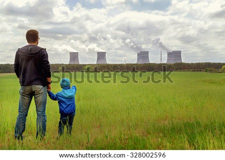 Pollution. Environmental problem. Father and his  son looking on a emissions of plant. Factory chimneys (smoke stacks) polluting air on green field. Nuclear power plant. Ecology concept. Copy space.