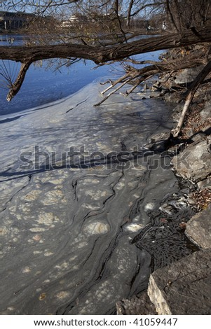 Pollution in the water on the river shore - stock photo