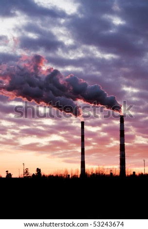 Pollution spewing into the air from industrial chimneys, at sunset.