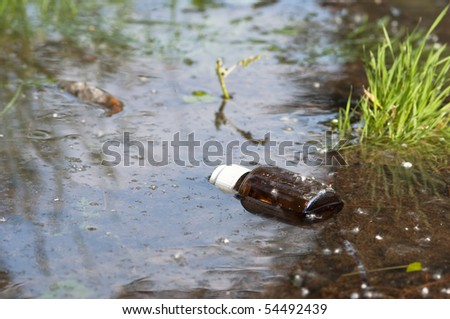 pollution water floating battle thrown away in the river - stock photo