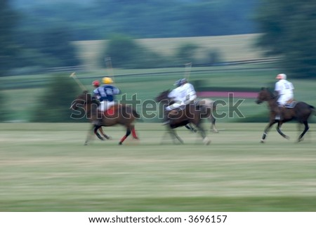 Polo Match at full gallop with intentional panning blur to emphasize speed - stock photo