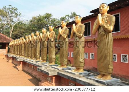 Polonnaruwa, golden statues of monks in Sri Lanka. - stock photo