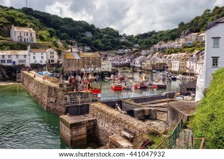 Polperro, Cornwall, England. The ancient fishing village showing the harbour with boats.
