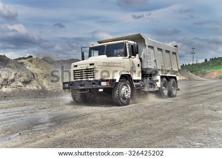 Poltava Region, Ukraine - June 26, 2010: Dump truck driving along the muddy road on the iron ore opencast