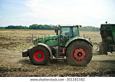 POLTAVA, UKRAINE - 29 JULY 2015: Tractor spreading manure on fields. This procedure allows to collect two harvests a year.