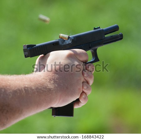 Polymer handgun that has delivered two fast shots - stock photo