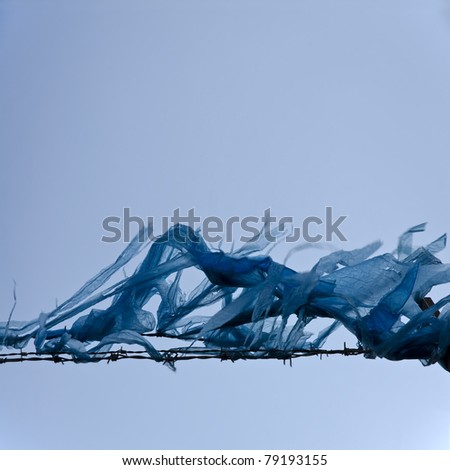 Polythene waste impaled on barbed-wire against blue sky; conceptual image of urban waste and trash; excellent copy space - stock photo
