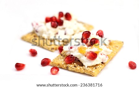 Pomegranate and apricot cream cheese dip on a cracker over white background. - stock photo