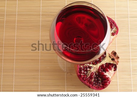 Pomegranate and glass of red wine close-up on mat.