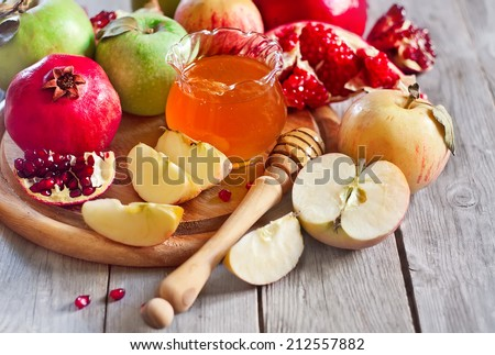 Pomegranate, apple and honey, traditional food of jewish New Year celebration, Rosh Hashana. Selective focus.