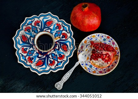 Pomegranate fruit and fresh coffee. Breakfast with ceramic turkish plates in traditional style. - stock photo