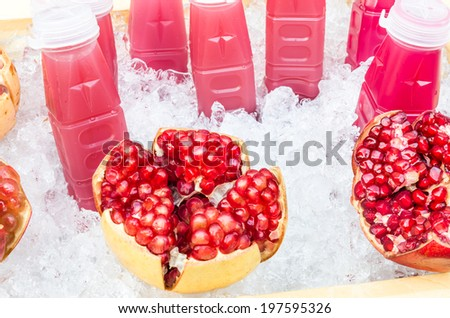 Pomegranate fruit and fresh juice bottles on ice - Concept of healthy and energetic multivitamin drinks - stock photo