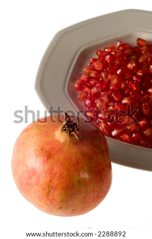 Pomegranate grains on dish isolated on white with whole pomegranate - stock photo
