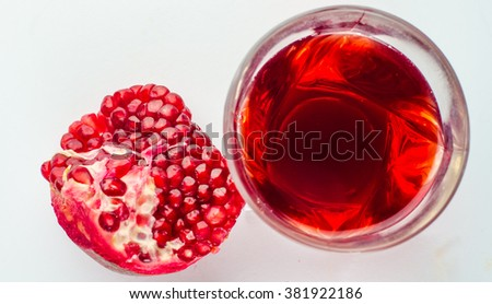 Pomegranate juice in a glass and ripe pomegranate. Isolated on white background,horizontal photo - stock photo
