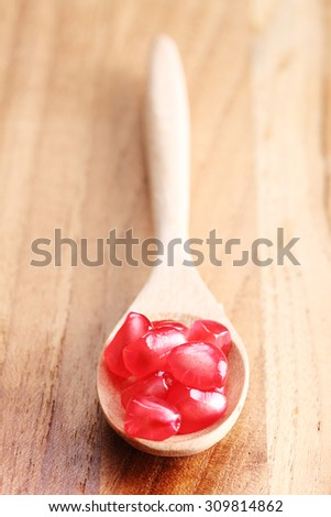 pomegranate, red juicy pomegranates in a spoon on wooden background - stock photo